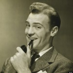 Businessman holding pipe in mouth, smiling, (B&W), portrait